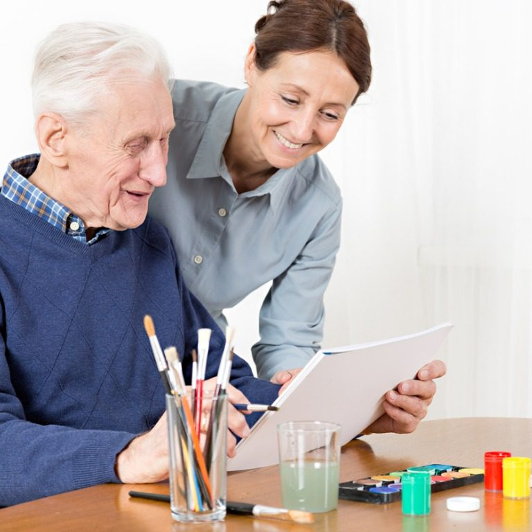 Caregiver with Elderly Man Getting Ready to Paint a Drawing with a Bible Verse