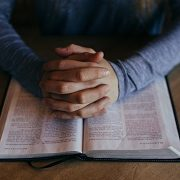 Praying Hands Resting on an Open Bible